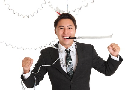 Happy party guy wearing a suit and tie, with a party hat. Party horn blower in his mouth. White background. Stock Photo