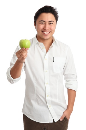 Young man holding a green apple. Wearing a white shirt. White background. photo