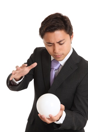 Businessman with a glassball, looking in to the future. White background. Stock Photo - 17424682