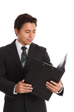 Businessman checking the numbers. Young businessman looking in a folder. White background. photo