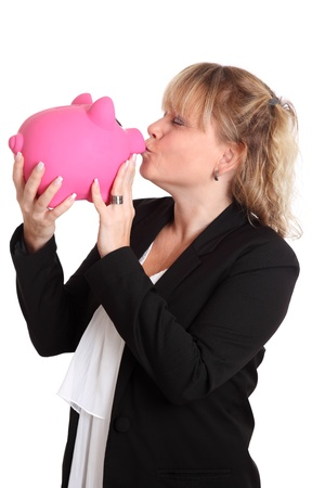Female kissing a pink piggybank wearing a suit and white shirt. White background. photo