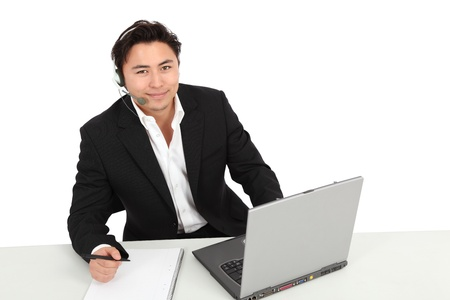 Young man working, with a laptop and headset. Wearing a suit and white shirt. White background.