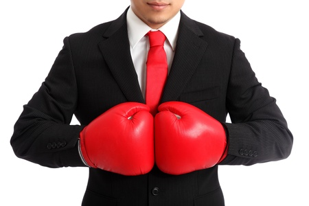 Businessman wearing red boxing gloves and a black suit with a red tie  White background  Stock Photo