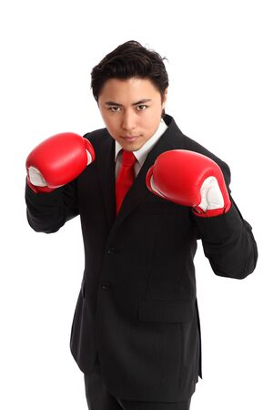 Businessman wearing red boxing gloves and a black suit with a red tie  White background  photo