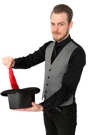 Magician performing with a red handkerchief and top hat  Wearing a black shirt and vest  White background