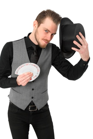 Magician holding a card fan and top hat  Wearing a black shirt and vest  White background