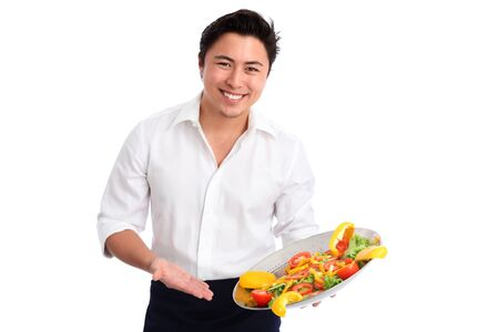 chef knife: Young chef wearing a White shirt and apron  Preparing a salad  White background  Stock Photo