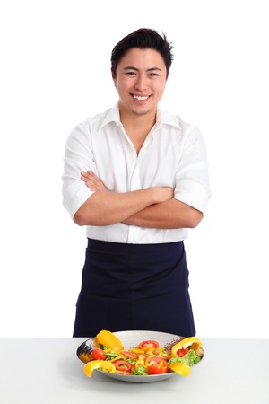 Young chef wearing a White shirt and apron  Preparing a salad  White background  Stock Photo