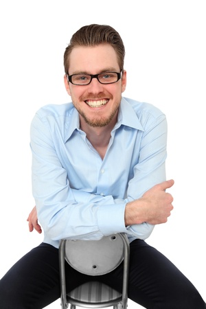 Smiling Young man wearing glasses and a blue shirt  Sitting down  White background  photo