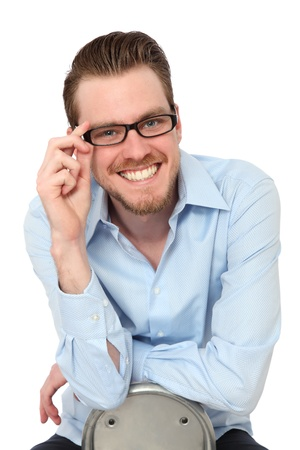 Smiling Young man wearing glasses and a blue shirt  Sitting down  White background