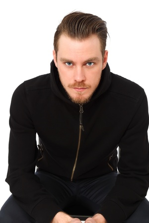 good looking model: Young confident man sitting down wearing a black hoodie  White background