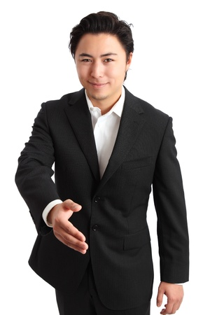 Young relaxed businessman wearing a suit reaching out for a handshake  White background