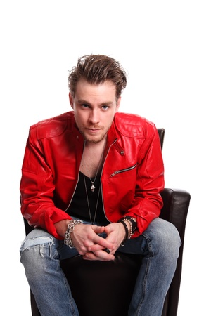 Cool looking rocker guy wearing a black tank top and a Red leather jacket, with torn jeans  White background