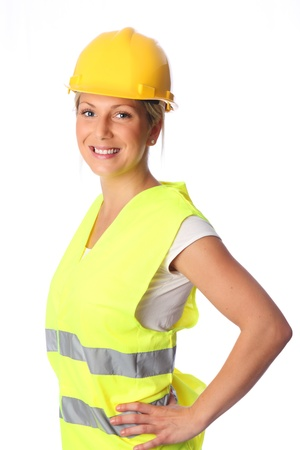 Young attractive female construction worker wearing a reflective vest and hard hat  White background