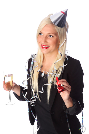 Attractive woman wearing a black party dress, party hat and streamers  Holding a champagne glass and blower  White background  photo