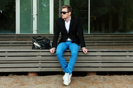 A man sitting outside wearing black sunglasses and a black jacket with blue jeans