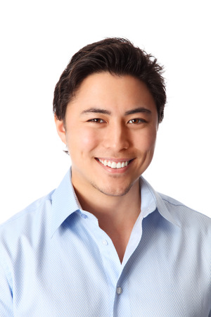Young good looking man standing wearing a blue shirt  White background  Stock Photo