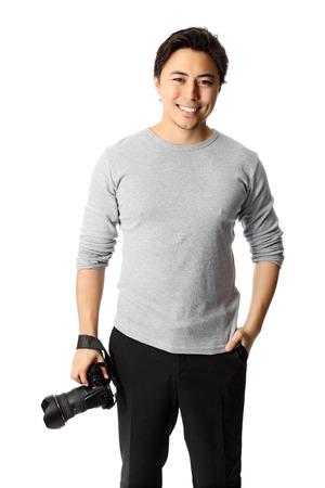 Good looking young man wearing a grey shirt holding a digital camera   Stock Photo