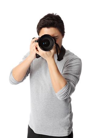 Good looking young man wearing a grey shirt holding a digital camera