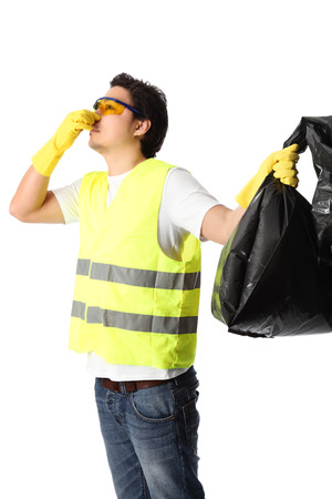 Young standing wearing a reflective vest, gloves and safety glasses  Holding a black garbage bag  White background  photo