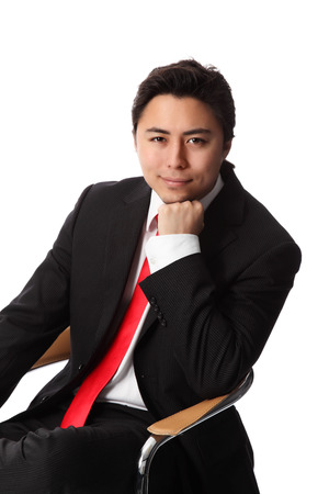 Young serious businessman sitting down in a chair wearing a suit and red tie  White background  Stock Photo
