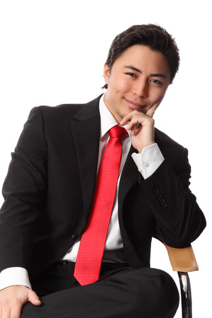 Young serious businessman sitting down in a chair wearing a suit and red tie  White background  photo