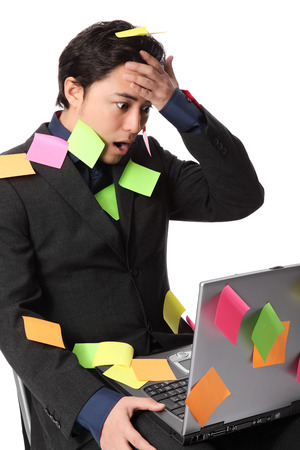 Frustrated businessman with lap top and post it notes all over him  White background  photo