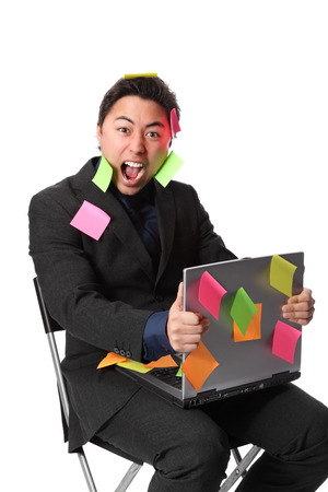 lap top: Frustrated businessman with lap top and post it notes all over him  White background