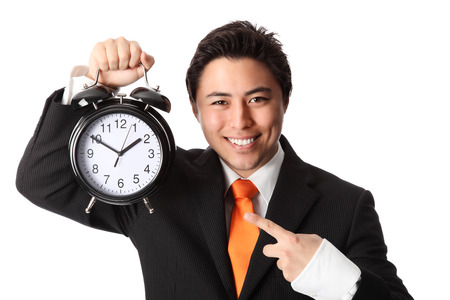 Attractive businessman holding a clock, wearing a suit and orange tie  White background  photo