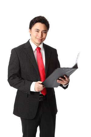 Young attractive businessman standing wearing a suit and red tie  Holding a document folder  White background