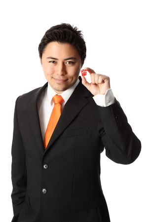 Attractive businessman in a suit and tie, holding red dices, taking a risk  White background  Stock Photo