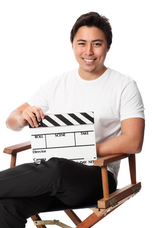 Young attractive man holding a film slate, wearing a white t-shirt  White  photo