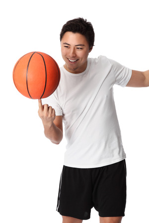 Young attractive basketball player wearing a white tshirt with black shorts, holding a basketball  White background