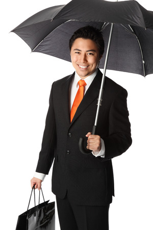 Good looking young businessman wearing a suit and tie, standing under an umbrella  White background  photo