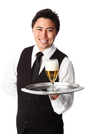 Young attractive waiter wearing a white shirt and black vest, serving a nice cold beer  White background
