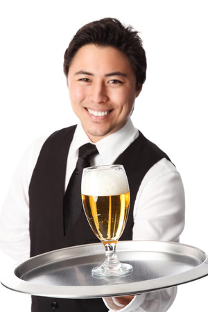 Young attractive waiter wearing a white shirt and black vest, serving a nice cold beer  White background  photo
