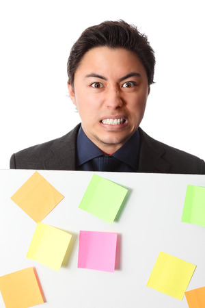 Attractive businessman holding a board with post it notes on it  White background  photo