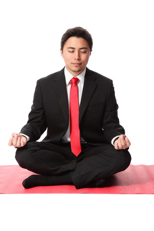 Attractive businessman praying for a great year  Wearing a suit and tie, sitting on a yoga mat  White background