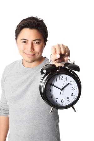Young attractive man holding a clock photo