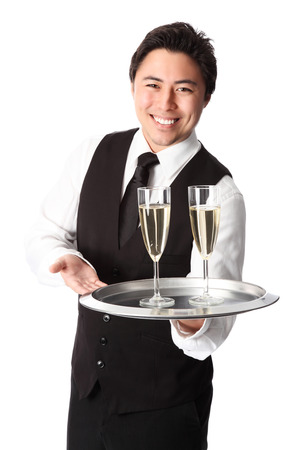 Attractive waiter serving 2 glasses of champagne 写真素材