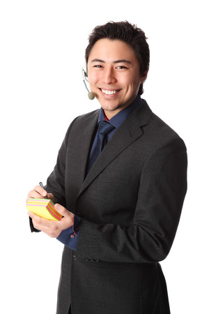 Attractive businessman wearing a head set holding a note pad photo