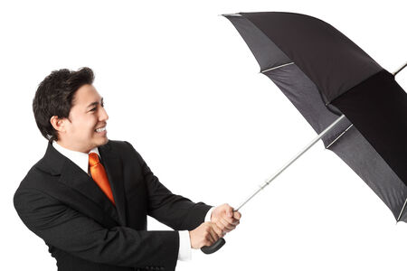 Businessman in a suit and tie, holding an umbrella trying not to blow away  White background  photo