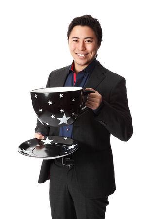 przewymiarowany: Przystojny biznesmen gospodarstwa ponadgabarytowych filiżanki kawy, ubrany w garnitur i krawat Białe tło
