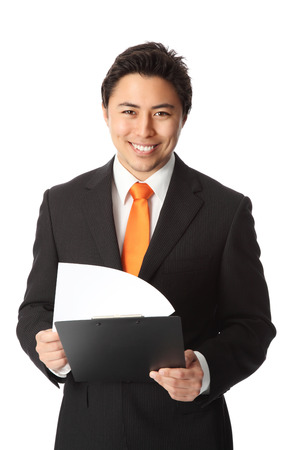 Young attractive businessman wearing a black suit and orange tie  Holding a clipboard
