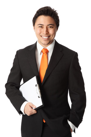 Young attractive businessman wearing a black suit and orange tie  Holding a clipboard  White background
