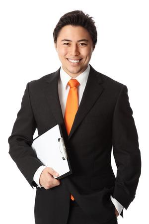 黒のスーツとクリップボードに保持オレンジのネクタイを身に着けている若い魅力的なビジネスマン ホワイト バック グラウンド