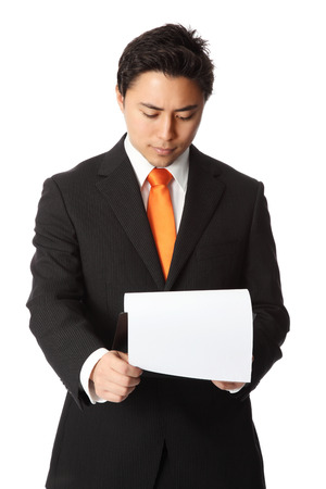 Young attractive businessman wearing a black suit and orange tie  Holding a clipboard  photo