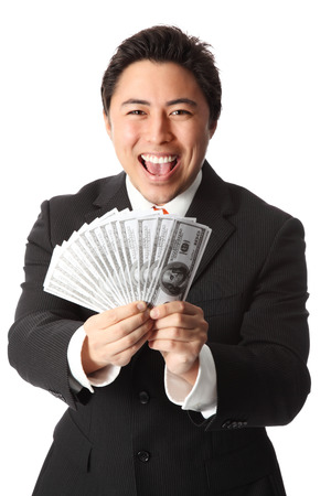 Attractive businessman wearing a suit and tie, holding a fan of hundred dollar bills  White background  photo