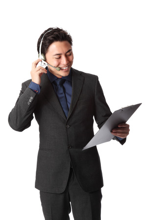 Serious businessman wearing a blue shirt and grey suit, holding a clipboard with a headset  White background  photo