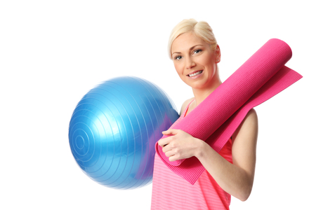 Attractive blonde woman holding a blue gym ball and pink yoga mat, wearing a pink top  White background  photo